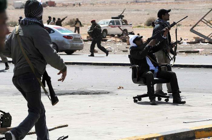 Вооруженный придурок на офисном стуле. Если бы не НАТОвские мерзавцы, правительственные войска смяли бы этих клоунов за неделю. Пригород Рас Лануф (Roberto Schmidt/AFP/Getty Images)