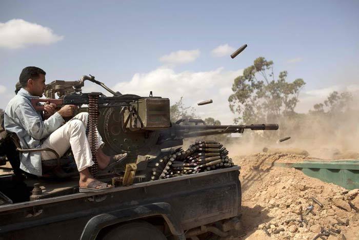 Дурачок в белых штанах и тапочках постреливает в сторону войск своей страны в 25 км к западу от Мисураты, Ливия, 23 мая 2011 года. (AP / Rodrigo Abd)